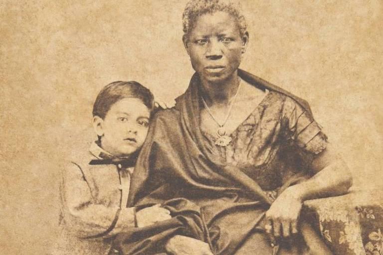 imagem em preto e btanco mostra mulher negra posando para foto sentada. Ao lado dela, há uma criança branca