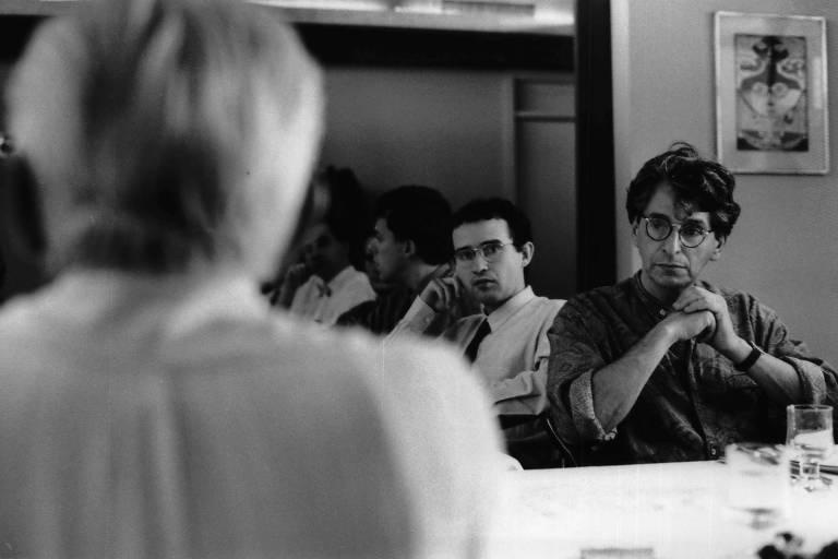 em primeiro plano, homem de cabelos brancos, de costas, olha para frente; em segundo, dois rapazes jovens o observam do outro lado de uma mesa