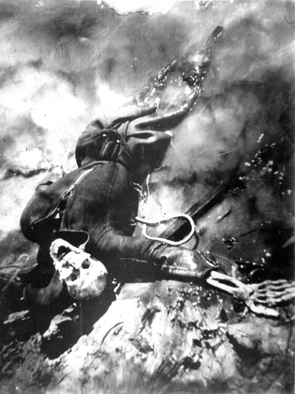 esqueleto vestido com roupa de mergulhador flutua na beira de um rio