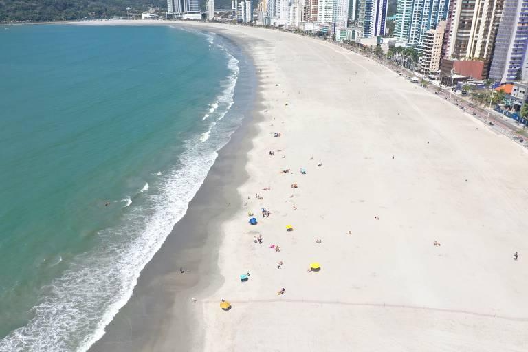 mar azul com uma larga faixa de areia e edifícios altos