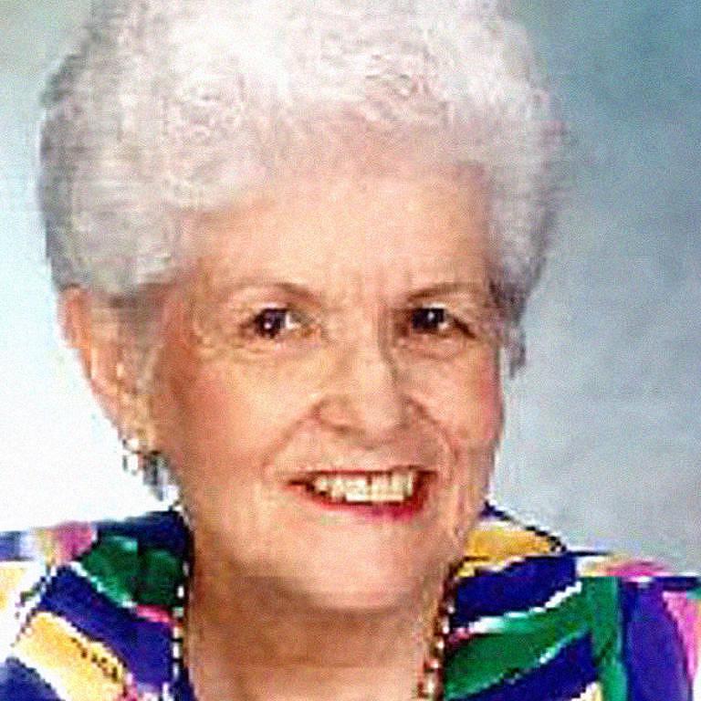 mulher branca, de cabelos muito brancos, posa para foto sorrindo. ela veste roupas coloridas, com estampa azul, verde, amarela e vermelha e usa um colar cumprido de contas brancas