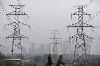 People walk past electricity pylons in Shenyang