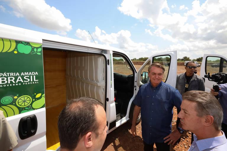 Jair Bolsonaro ao lado de uma van junto a aliados políticos