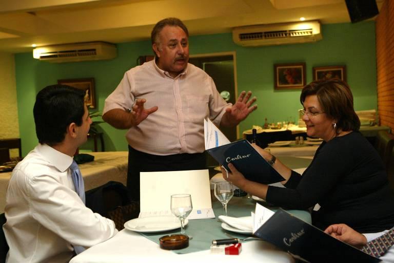 Dois clientes sentados à mesa de um restaurante observam um menu enquanto são atendidos por um homem em pé