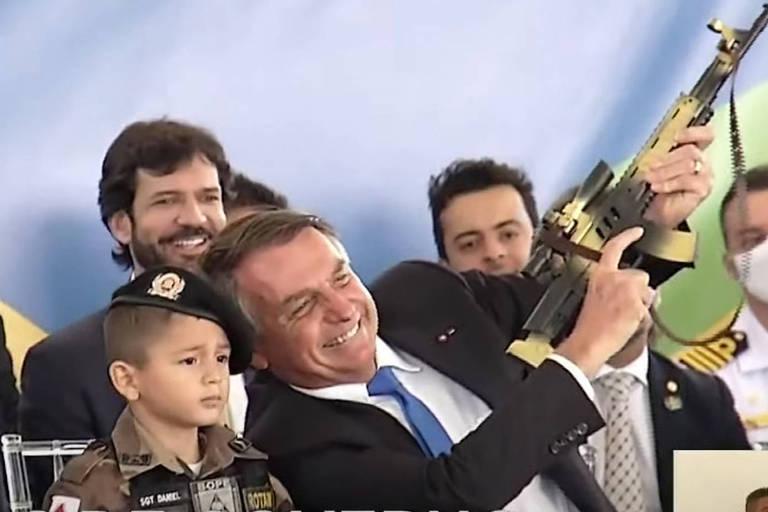 Bolsonaro está ao lado de menino vestido de soldado e com outros homens ao redor; ele segura uma arma camuflada de brinquedo, apontando-a para o alto