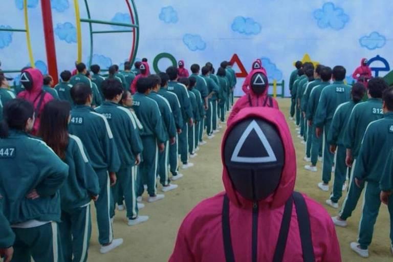 Pessoas em fila vestida de verde e outras com capuz e mascara de com triangulo