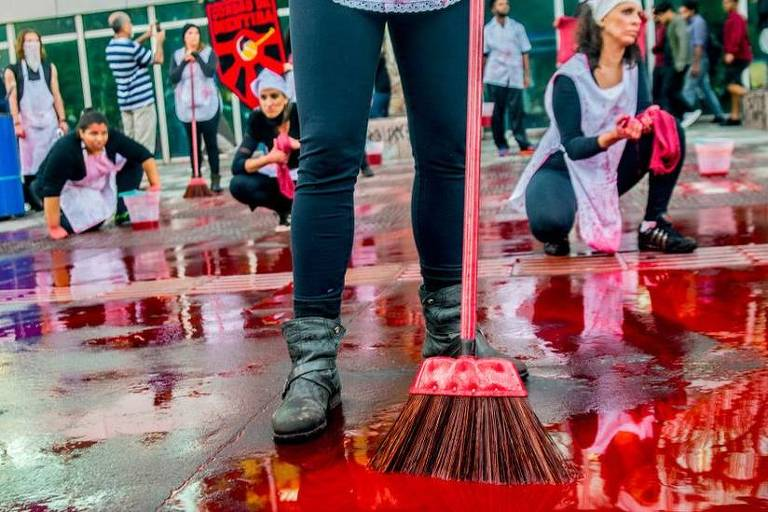 Em destaque, a imagem mostra as pernas de uma pessoa segurando uma vasoura. No chão, há tinta vermelha. Ao fundo, pessoas estão agachadas