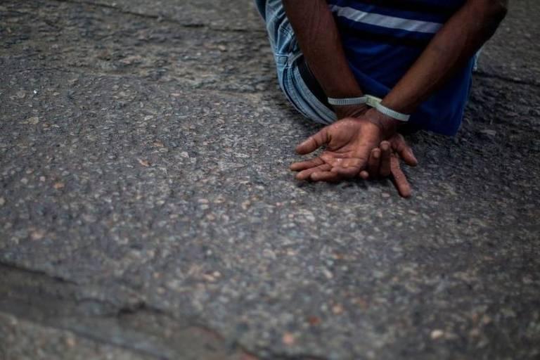 Imagem em close mostra as cotas de um hoemm negro sentado no chão com as mãos amarradas para trás.
