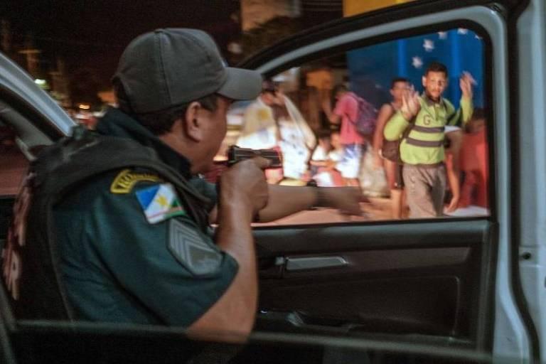 Imagem em primeiro plano mostra um policial apontando uma arma para um grupo de pessoas a sua frente. O agente está na janela de uma viatura.