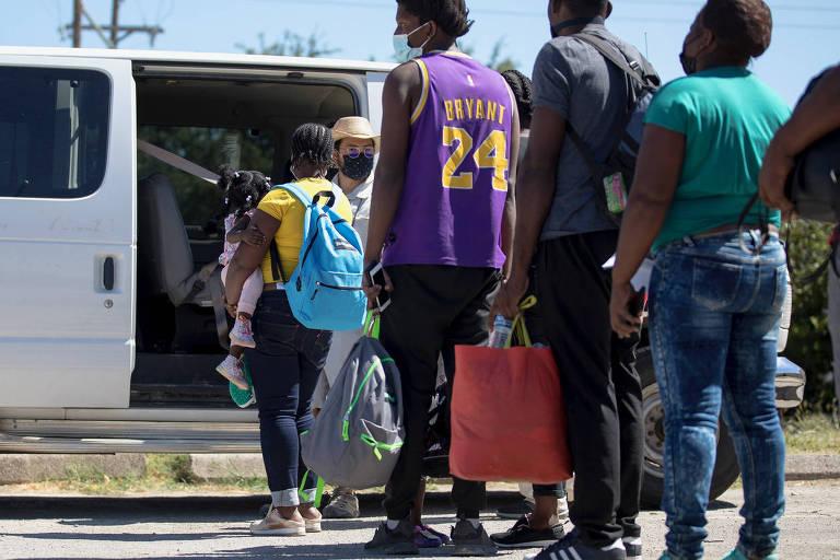Migrantes haitianos que chegaram ao Texas entram em van para serem deportados pelo governo dos EUA