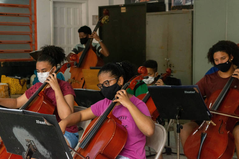 Jovens tocam instrumentos musicais.
