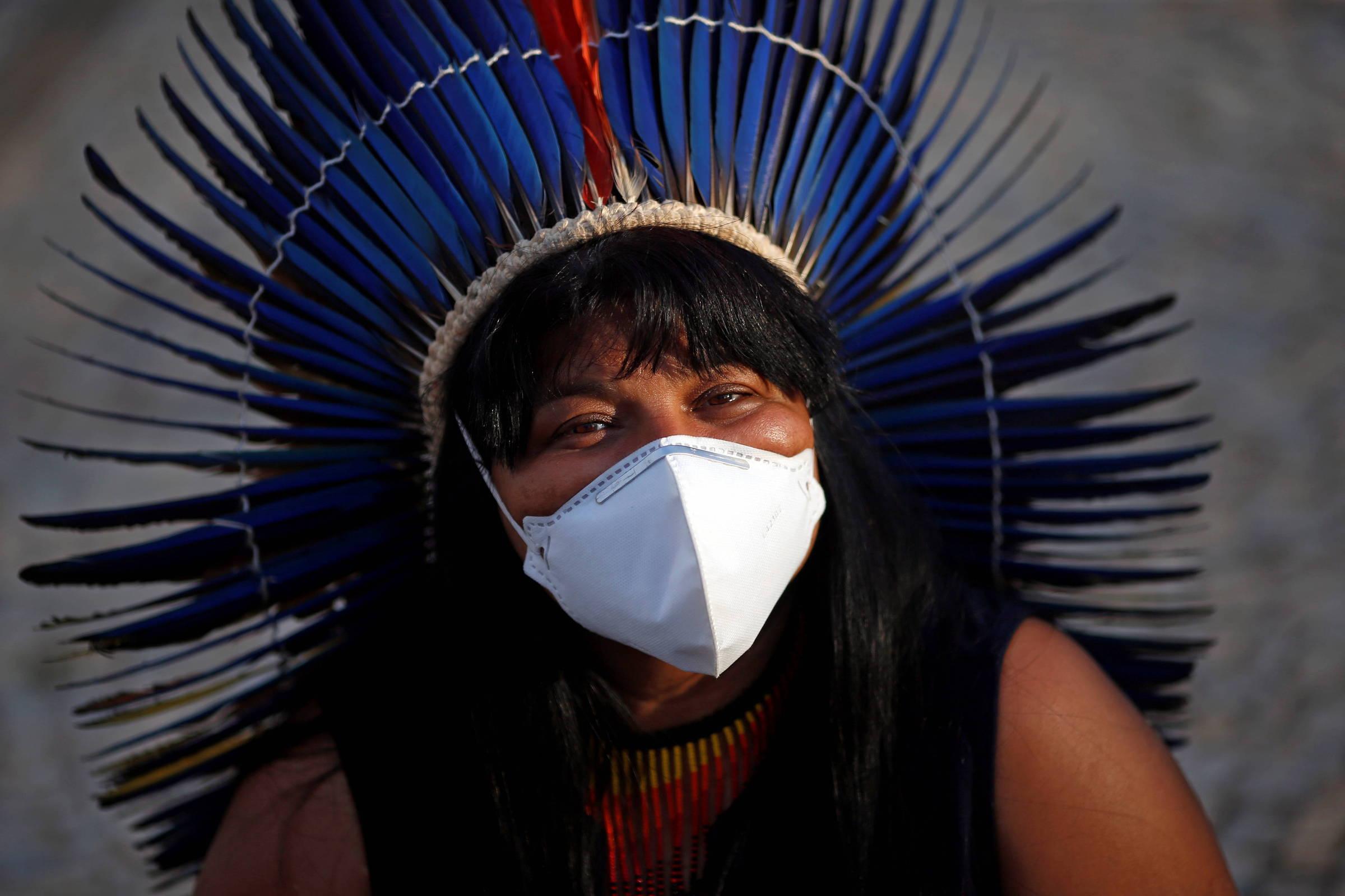 Sonia, de cocar azul e máscara branca, olha diretamente para a câmera, com um sorriso nos olhos