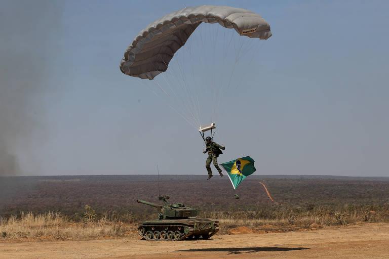 Militar pousa com para-quedas em campo próximo a um blindado