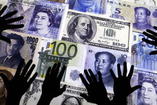 FILE PHOTO: Picture illustration of hands silhouetted against a backdrop projected with the picture of various currencies of money