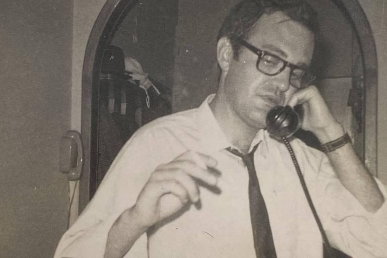 homem branco com camisa branca e gravata escura fina fala ao telefone e segura o cigarro
