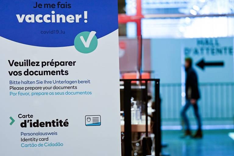 Homem passa ao fundo em corredor, com cartaz sobre vacinação em primeiro plano