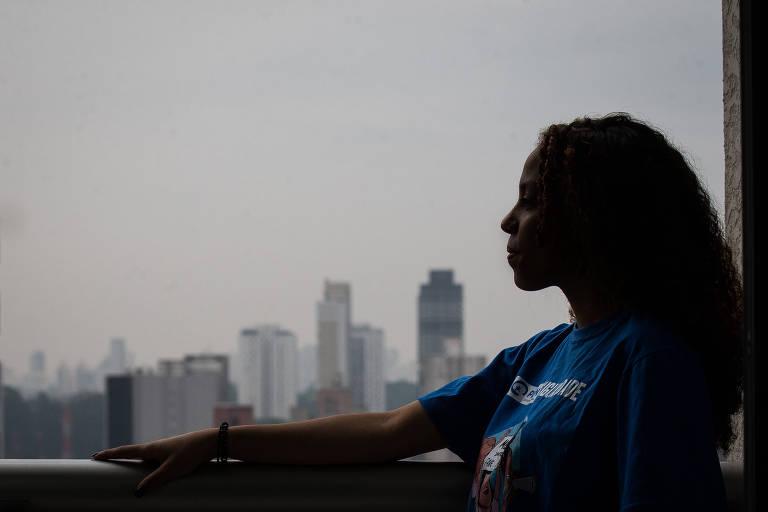 Silhueta de uma mulher negra de perfil, com camiseta azul, no canto direito da janela com a vista de São Paulo ao fundo. O céu está nublado e existem poucos prédios na parte inferior da foto, logo acima do batente da janela