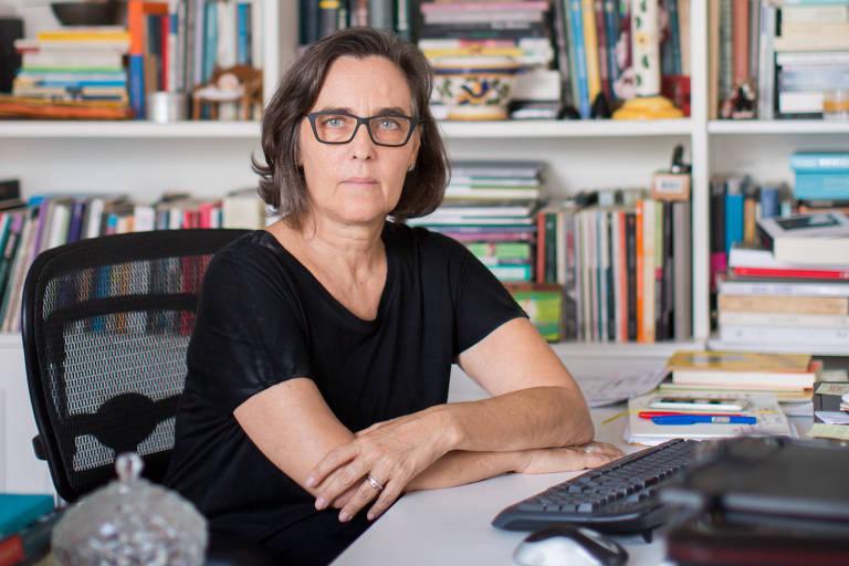 Uma mulher sentada em uma cadeira com uma mesa a sua frente. Ao fundo, uma estante com livros.