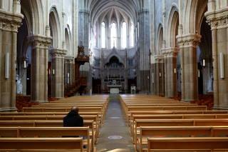A man prays inside the Saint-Martin church in Vertou