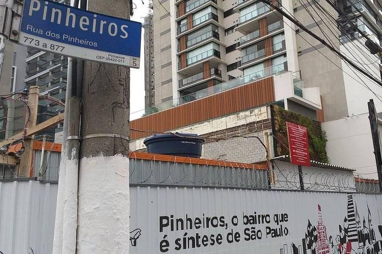 """No canto esquerdo da imagem, há um poste e uma placa de rua escrito """"Pinheiros"""". Ao fundo, se vê prédios e um muro onde se lê: """"Pinheiros, o bairro que é síntese de São Paulo""""."""
