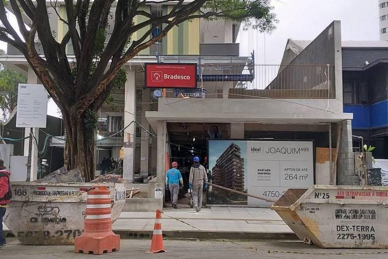 Imagem mostra fachada de uma obra. Na rua, há duas caçambas de entulho