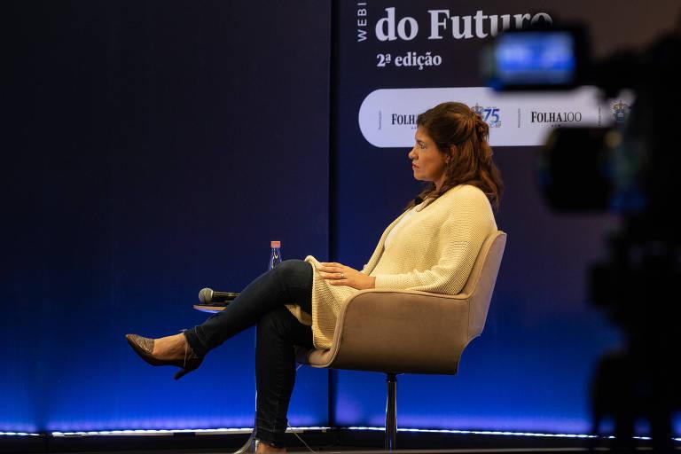 Repórter da folha, Erica Fraga, aparece sentada em uma cadeira no Auditório Folha. Ao fundo, uma tela azul exibe a frase 'Universidade do Futuro'