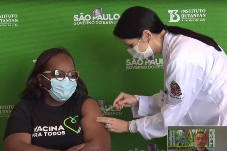 A enfermeira Monica Calazans toma a terceira dose de Coronavac durante a coletiva do governador João Doria