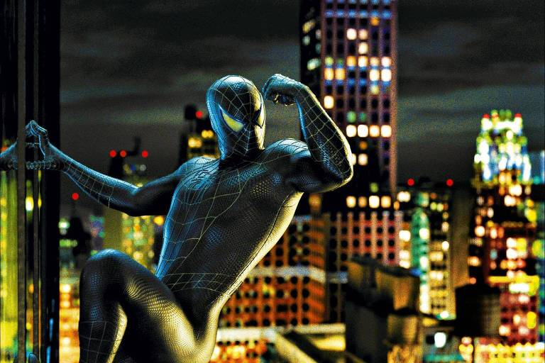 Com fatasia preta o ator aparece escalando um prédio