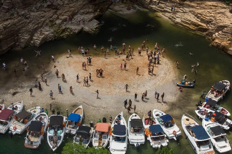 Imagem mostra 16 embarcações ao redor de uma área com dezenas de turistas. Local, que possui formação rochosa e é rodeado por água, ficou visível após o nível da represa de Furnas diminuir