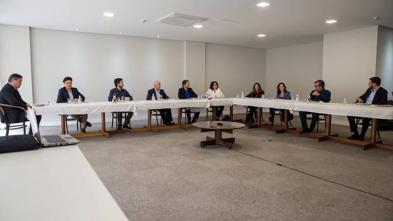 Em uma mesa em L comprida e toalha branca estão sentados da esquerda para a direita, Joel Pinheiro da Fonseca, Persio Arida, Luiz Frias, Fernanda Diamant, Patrícia Campos Mello, Patricia Blanco, Hélio Schwartsman e Sérgio Dávila
