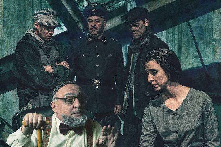 Um senhor e uma mulher sentados e três homens ao fundo