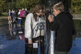 Visitors listen to the audio portion of the Mirror Field memorial at the Babyn Yar Holocaust Memorial Site in Kyiv, Ukraine on Sunday, Oct. 3, 2021. (Brendan Hoffman/The New York Times)