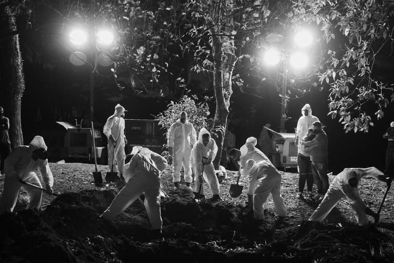 Homens usando roupas brancas abrem a terra com pás em meio a um cenário escuro, iluminado apenas por dois focos de luz. Há árvores sombrias no entorno