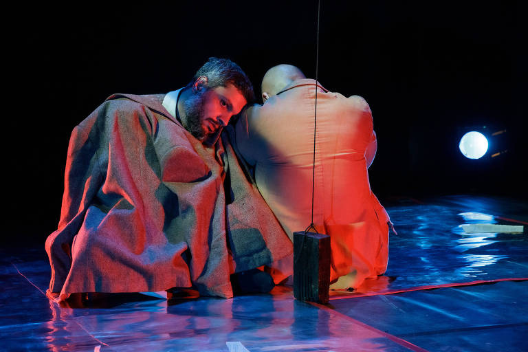 Dois homens sentado no chão, um virado para frente e outro de costas