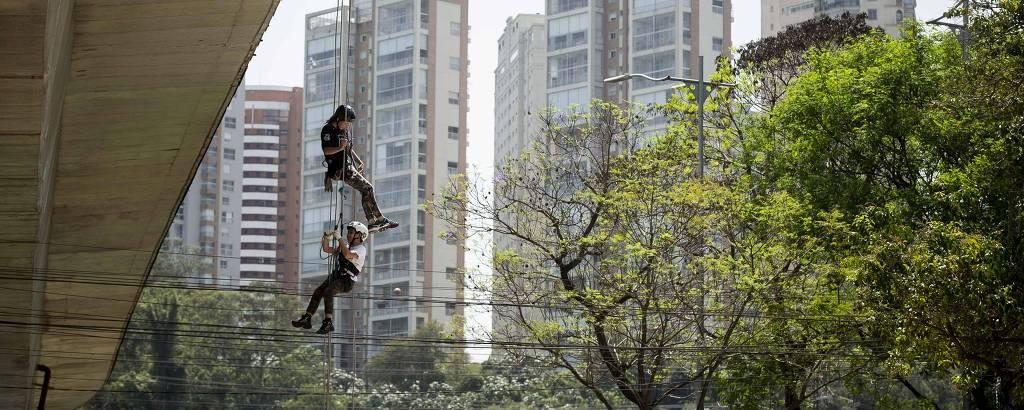 Criança e instrutor fazem rapel na Vertical Infinity, em São Paulo