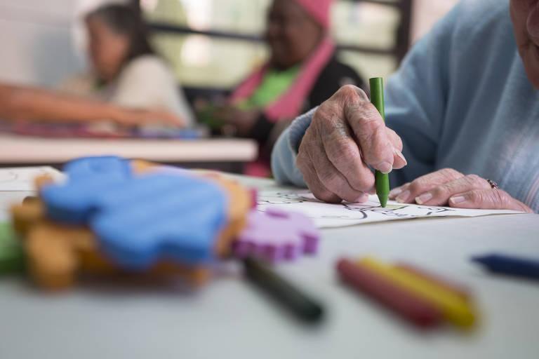 Imagem mostra mão de idosa pintando com giz de cera verde