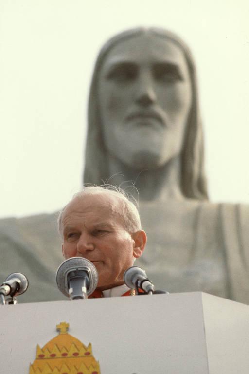 Homem idoso fala ao microfone em frente à estátua de Jesus Cristo