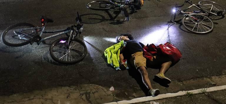 um homem deitado no chão com bicicletas caídas ao redor