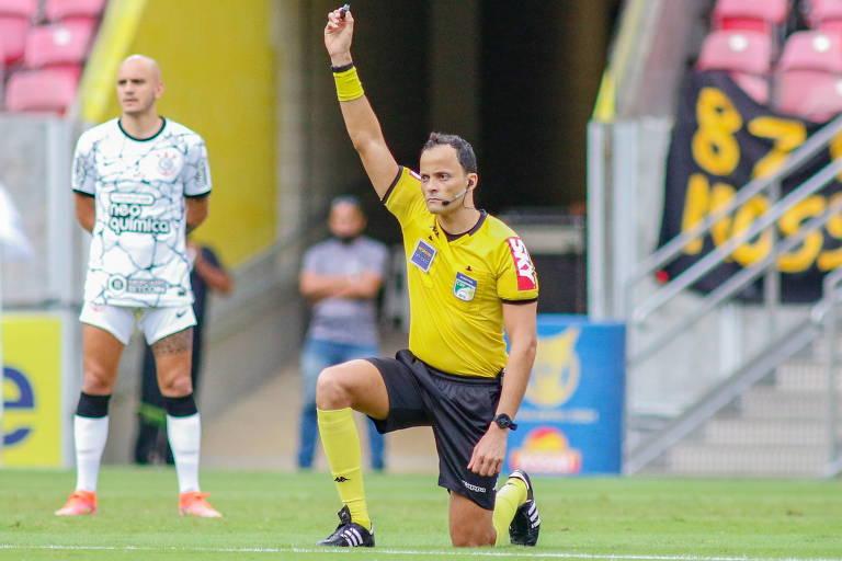 O árbitro Savio Pereira Sampaio se ajoelha e levanta seu apito, em protesto contra a agressão sofrida por seu colega de profissão Rodrigo Crivellaro, na Série B do Campeonato Gaúcho, na segunda (4)