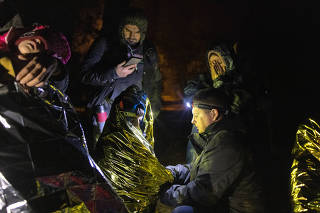 Piotr Bystrianin, center, who spends his nights searching for migrants, aids a family in Poland near the border with Belarus early on Oct. 2, 2021. (Maciek Nabrdalik/The New York Times)