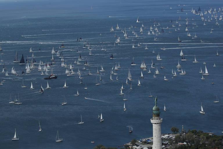 Visão aérea mostra dezenas de barcos brancos em baía