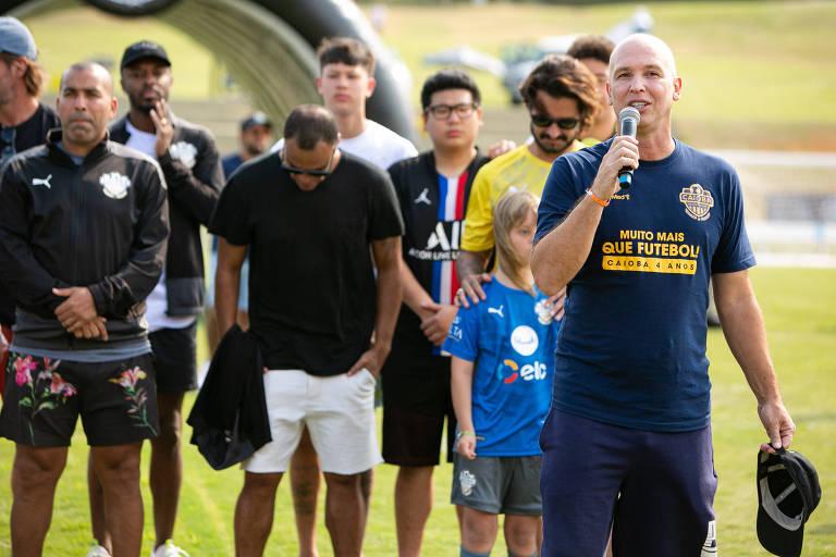 Caio Ribeiro, com microfone em mãos, e sem cabelos em razão de um tratamento contra o câncer, promove edição do Caioba, evento que reúne quase 300 crianças praticando atividades
