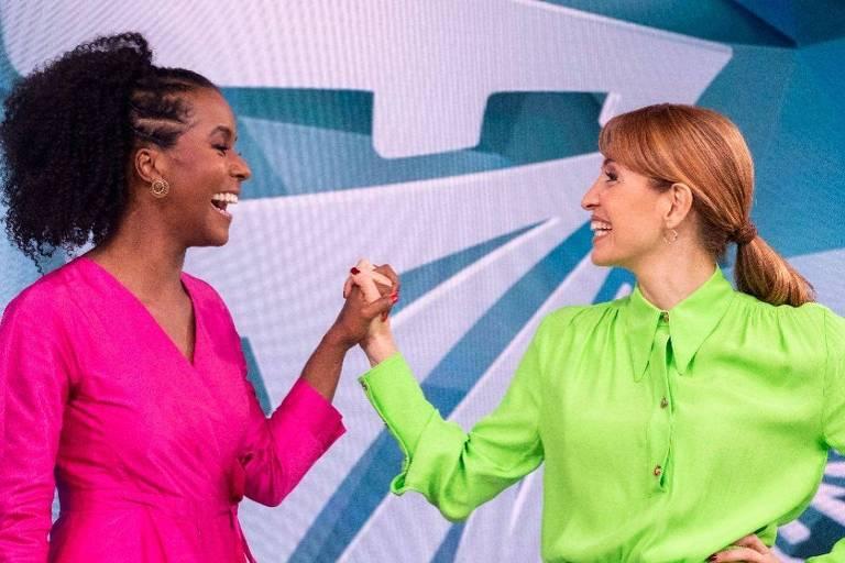 Mulher negra usando vestido rosa neon de mãos dadas com mulher branca usando vestido verde neon, ambas em frente à um painel azul com a logo do programa Fantástico