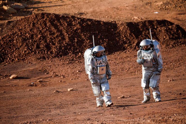 Duas pessoas com roupas brancas de astronauta em meio a rochas avermelhadas