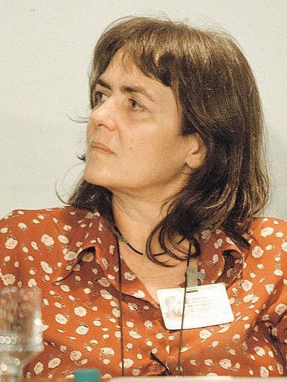 mulher branca veste blusa marrom com bolinhas brancas. ela está sentada e olhando para o lado