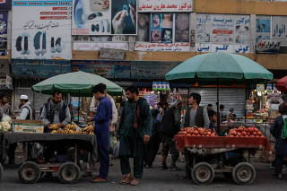 People buy fruits at a market in Kabul