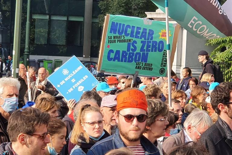 Passeata com muitas pessoas em que uma delas segura cartaz defendendo a energia nuclear
