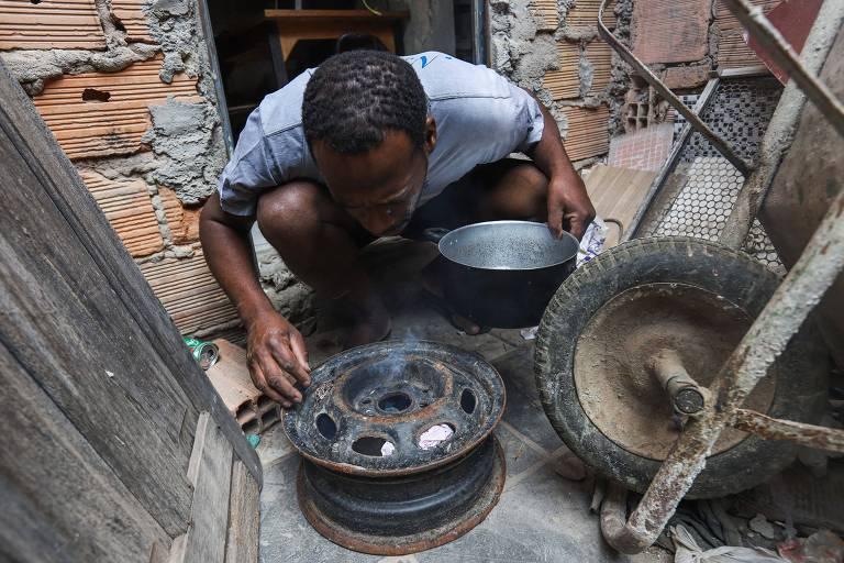 Ederson Vieira Estevão, 40, acende o fogareiro improvisado com uma roda de carro avelha