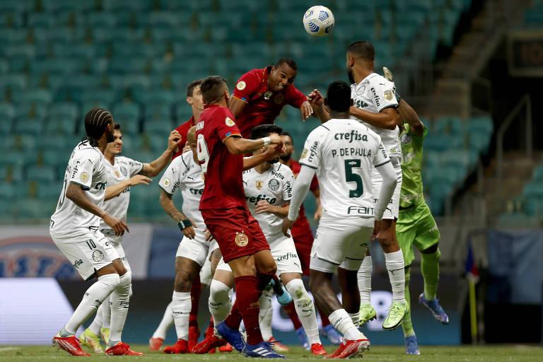 Jogadores de Palmeiras e Bahia disputam bola aérea durante partida na noite desta terça (12), em Salvador