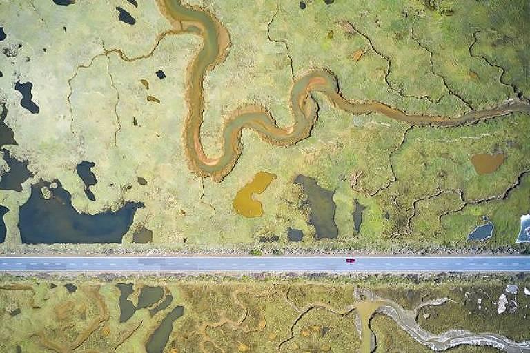 Imagem mostra a linha reta de uma estrada cortando as curvas de uma paisagem pantanosa que abriga mais de uma centena de espécies de pássaros